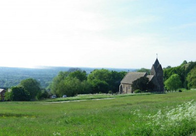 Meadow in the foreground, small church in the mid-distance and valley with farmland beyond.