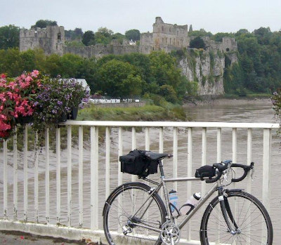 Bike stood by white railings and flower boxes with ruined castle in the background.