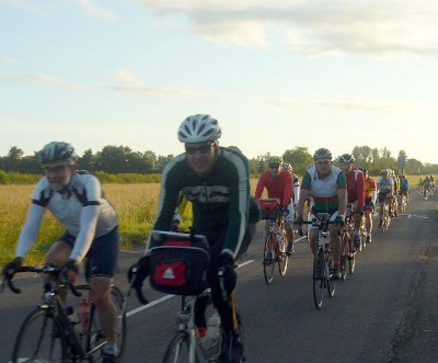 Large group of cyclists on the road in dawn sunlight.