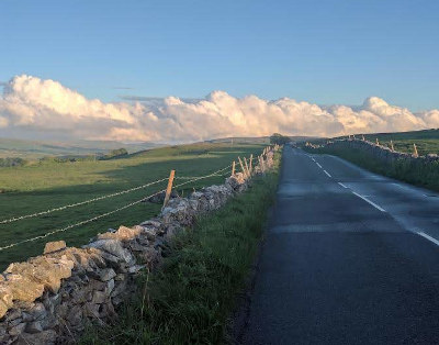 Road with dry stone wall stretching into distance with bright blue sky above cumulous clouds on the horizon.