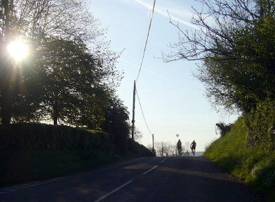 Cyclists cresting a hill in early morning sunlight with hot air balloon behind.