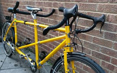 Yellow tandem leaning against a brick wall.