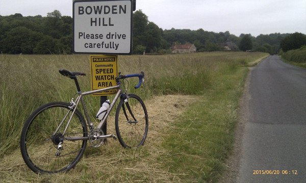 Bike and Bowden Hill sign. Meadow, grey skies.