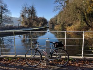Hybrid bike with rack bag by canal