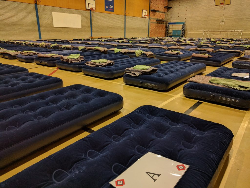 Large school sports hall with many mattresses ready