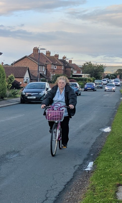 Woman on shopping bike with basket.